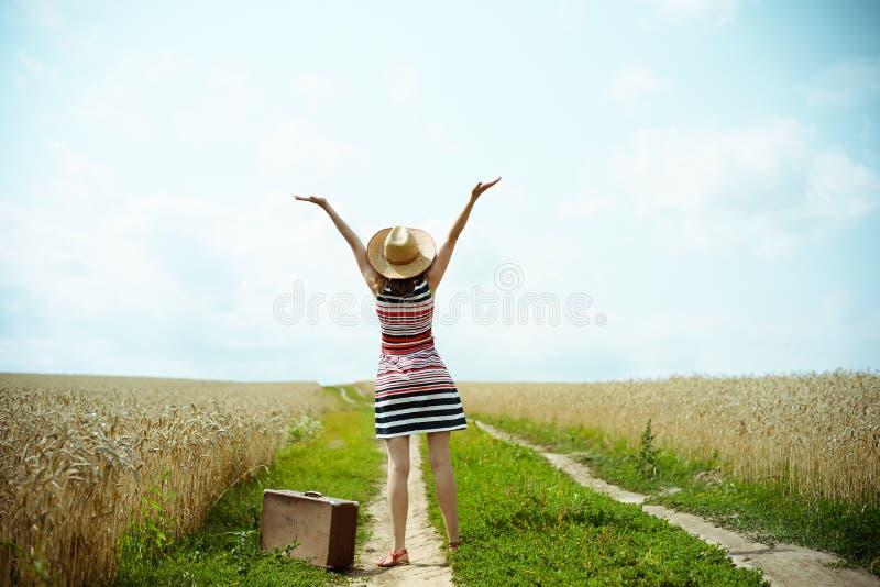Backview szczęśliwa kobieta z starym valize dalej zdjęcia stock