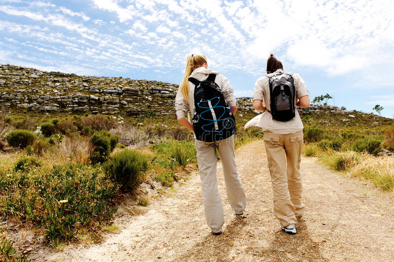 Backview of two young women hiking in nature royalty free stock image