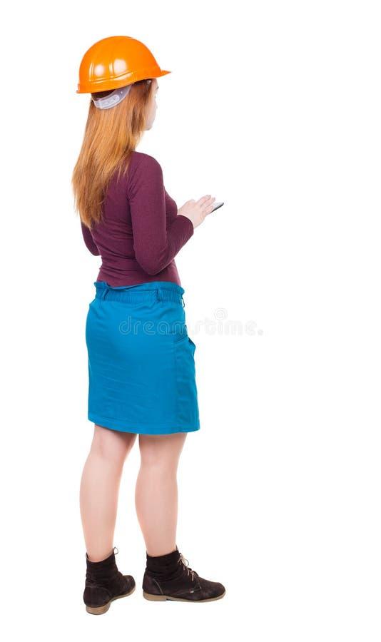 Backview van bedrijfsvrouw in de tribunes van de bouwhelm en enj stock fotografie