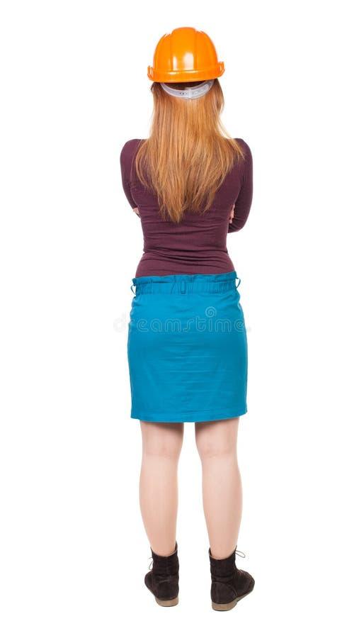 Backview van een vrouweningenieur in de tribunes van de bouwhelm stock foto