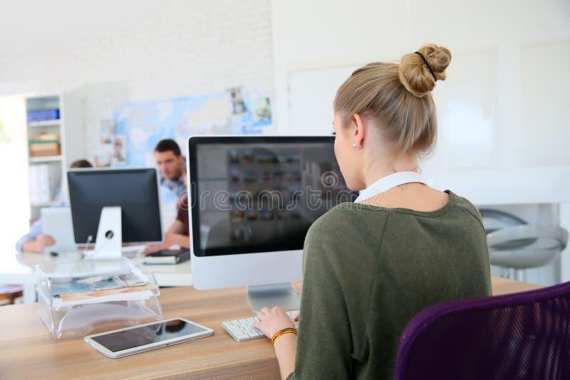 Backview van jong studentenmeisje die aan computer werken stock afbeelding