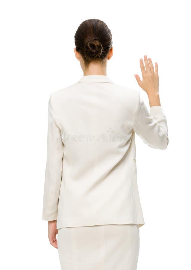 Backview van vrouwelijke uitvoerende golvende hand stock afbeeldingen