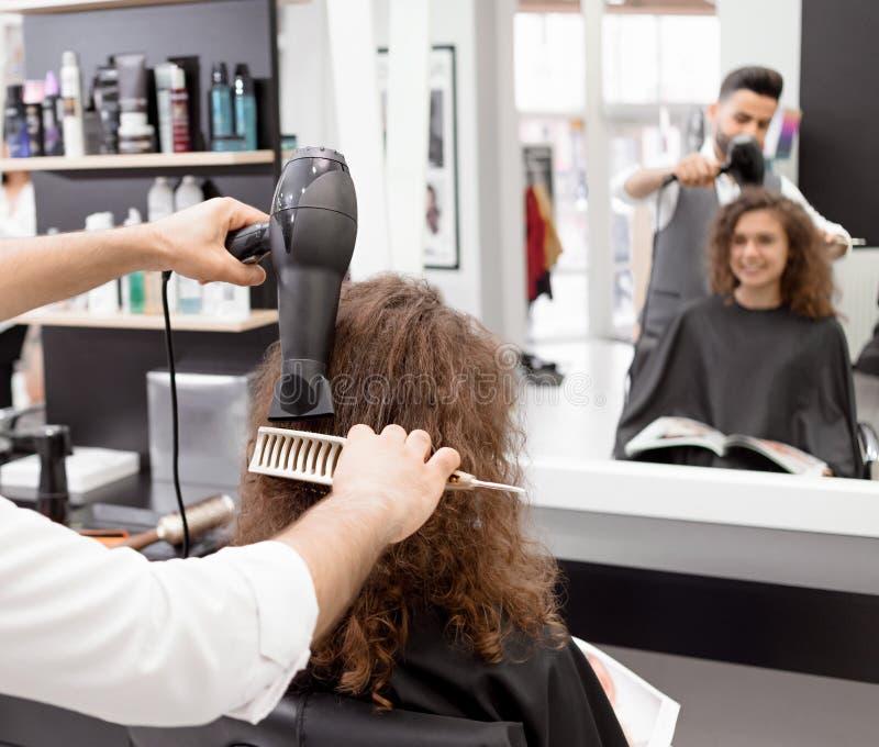 Backview von hairstyler weibliches Kunde ` s gelocktes Haar trocknend stockbilder