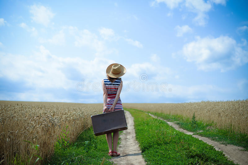 Backview of woman with suitcase on road in wheat stock photo