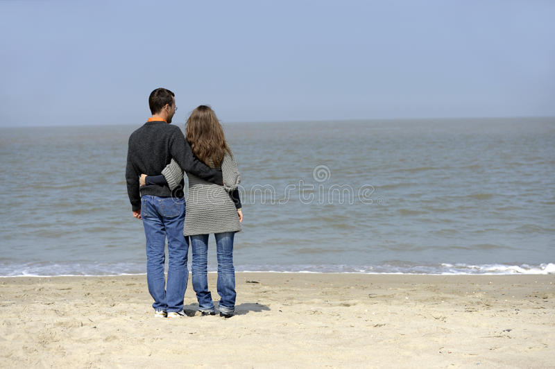 Backview of young couple at the beach royalty free stock image