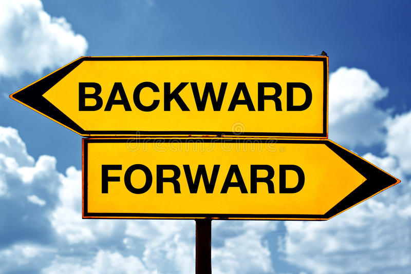 Backward or forward. Opposite signs. Two opposite signs against blue sky background stock image