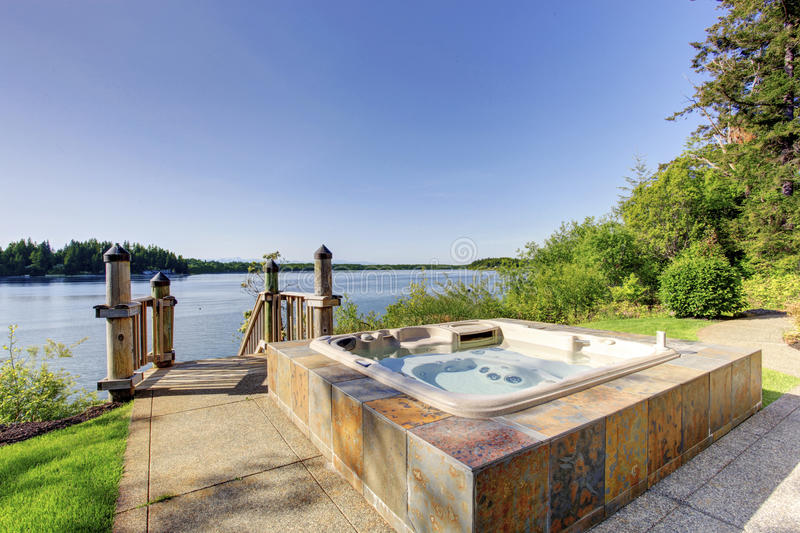 Backyard area with hot tub and awesome water view. Backyard area with awesome water view and hot tub with tile trim and concrete floor royalty free stock images