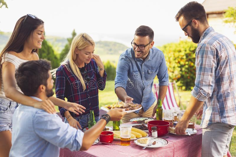 Backyard barbecue lunch. Group of friends having an outdoor barbecue lunch, eating grilled meat, drinking beer and having fun royalty free stock photos