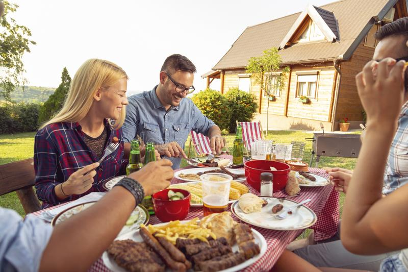 Backyard barbecue party. Group of friends having an outdoor barbecue lunch, eating grilled meat, drinking beer and having fun royalty free stock photos