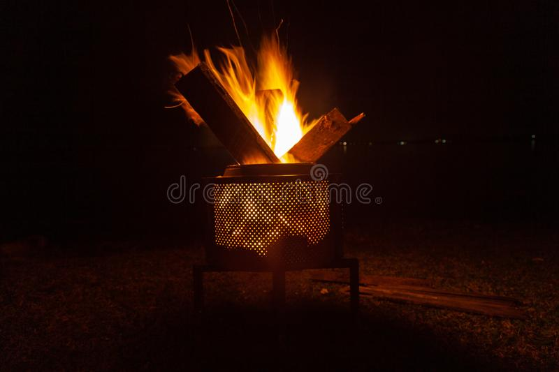Backyard campfire in brazier against night sky with lights in the background - , family fun in autumn or spring holidays. stock images