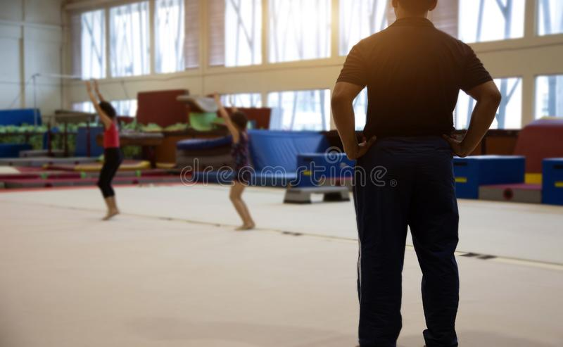 Backyard of coach in gymnastic kid practice in gym. Trainner sport concept, active, activity, apparatus, athlete, athletic, balance, beam, body, british royalty free stock photography