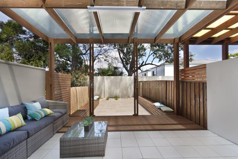 Backyard cozy patio area with wicker furniture set royalty free stock photos