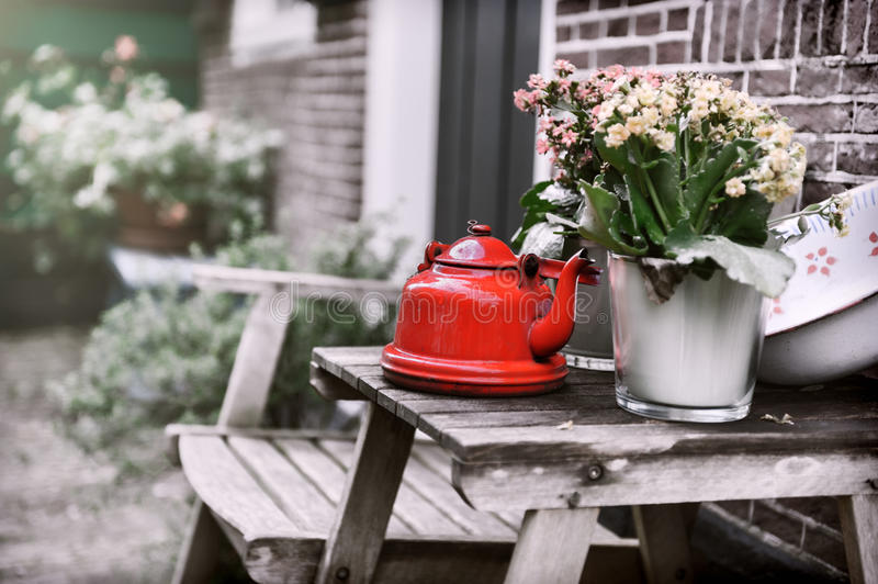 Backyard decoration with vintage kettle and flowers stock image