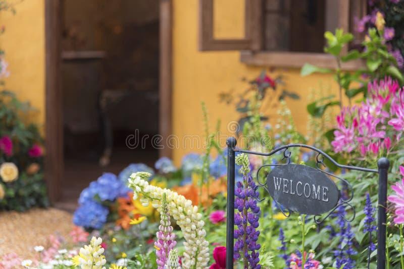 Backyard flower garden of residential house. Welcome home sign in backyard garden of residential house stock images