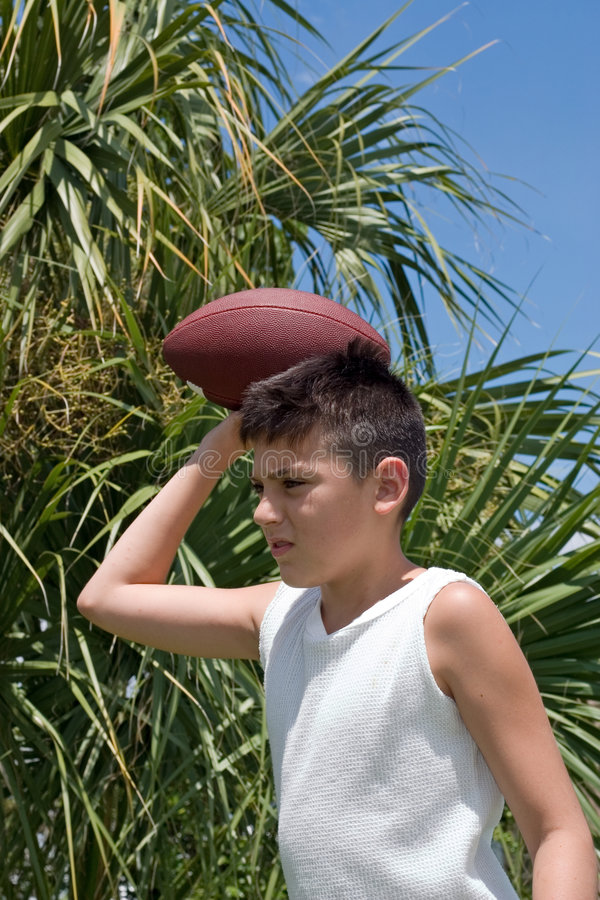 Backyard Football. Young boy practicing football with palm tree & blue sky background stock photography