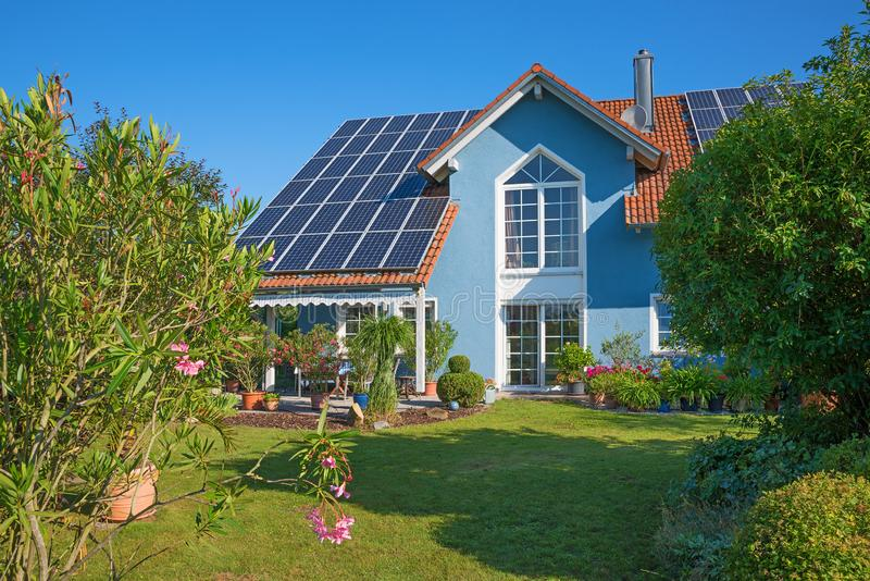 Backyard garden of a beautiful family home with solar panels on the roof royalty free stock photos