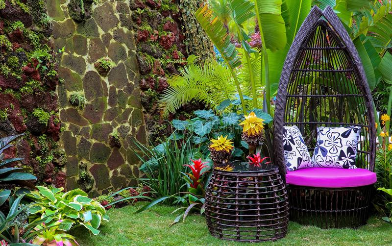 Asian backyard garden sitting area. Backyard garden of a house in spring season with flowering plants and furniture made of cane and flowering plants all around royalty free stock image