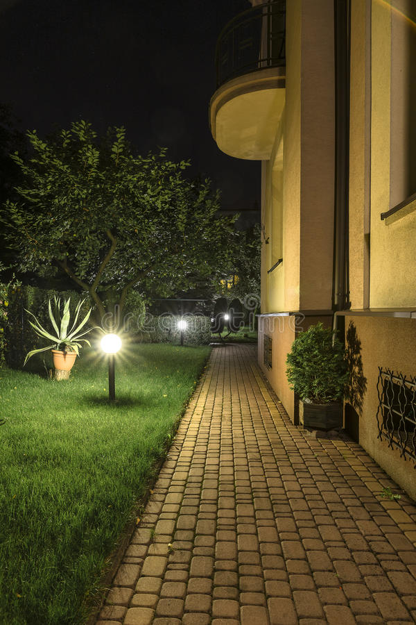 Backyard Garden Path at Night. Backyard Garden Path Brick with Lights at night with grass, trees royalty free stock photo