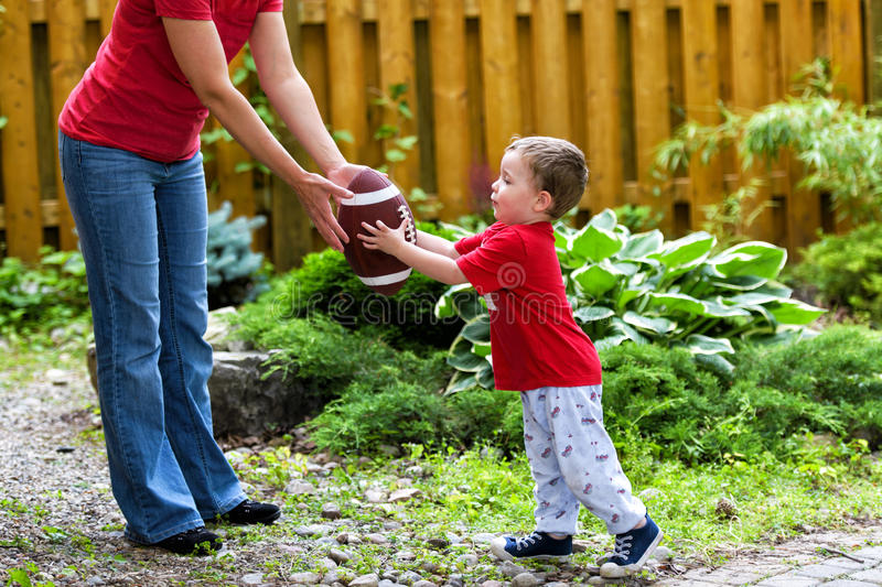 The Backyard Hand Off. A small boy receives a hand off from his mommy in a game of backyard football stock image
