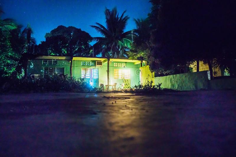 Backyard at night with house and lightened rooms, Bacalar, Mexico. Backyard at night with green house and lightened rooms and terrace, Bacalar, Mexico royalty free stock image
