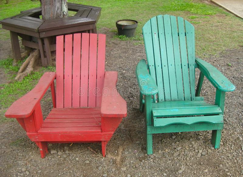 Backyard rustic wooden chairs in red and green. Two different styles of outdoor rustic wooden chairs in different colours royalty free stock photos