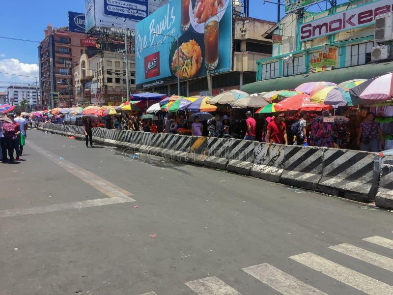 Baclaran, Metro Manila, Filipijnen - mei 2019 - Mensen die achter de betonnen barrières lopen met afval en afval op de weg V stock afbeeldingen