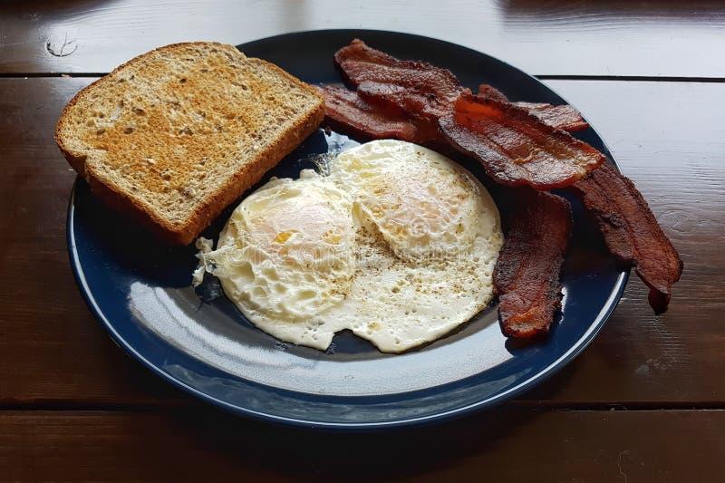 Bacon över lätta ägg och rostad brödfrukost för helt vete arkivbilder