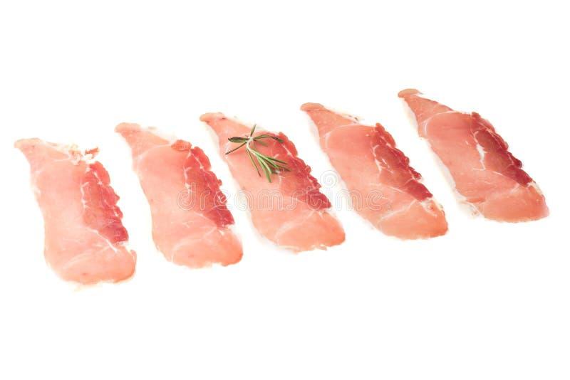Bacon affettato fresco della carne di maiale isolato su fondo bianco immagini stock libere da diritti
