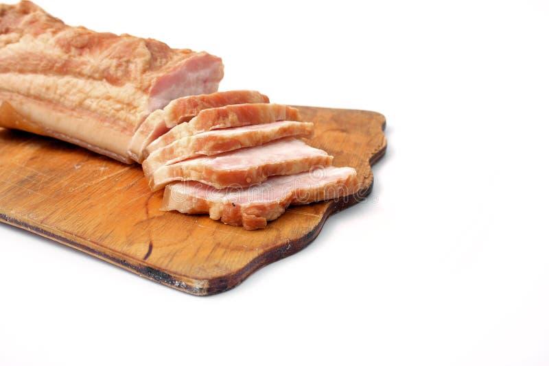 Bacon affettato su fondo bianco grasso della carne di maiale con le vene fotografia stock