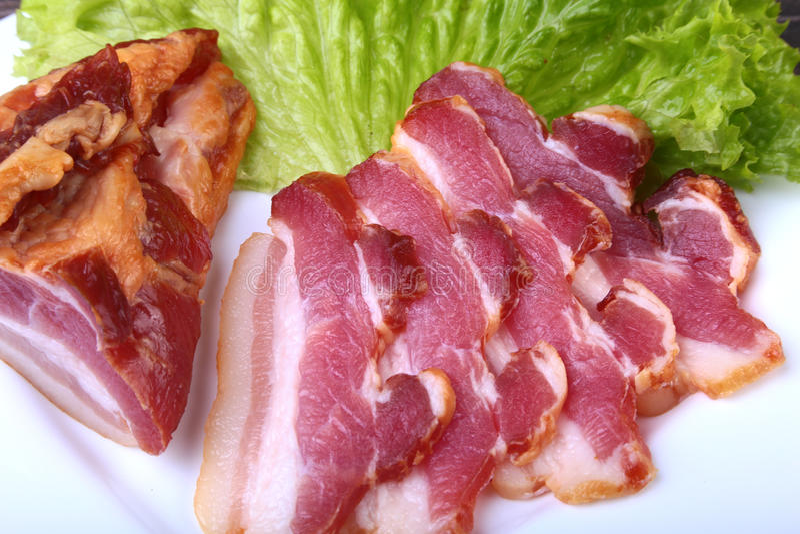 Bacon affumicato casalingo fresco con la lattuga di foglie sul piatto bianco Fuoco selettivo fotografia stock