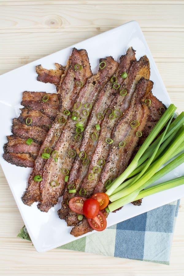 Bacon al forno del granello di pepe in piatto ceramico bianco quadrato immagini stock