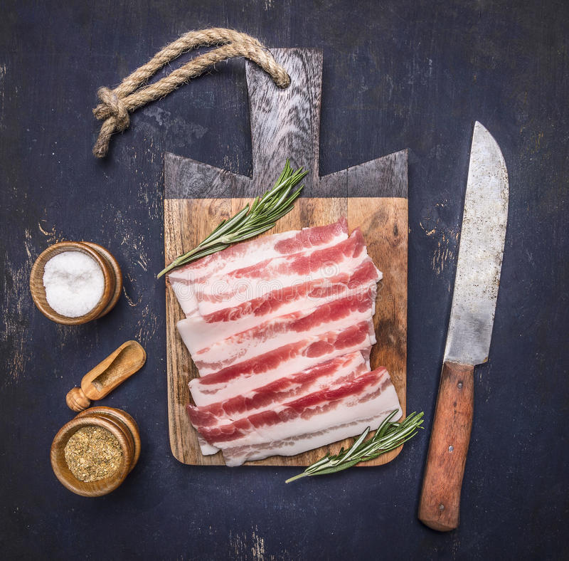 Bacon, alecrins, faca e especiarias crus deliciosos em um fim rústico de madeira da opinião superior do fundo da placa de corte a imagem de stock royalty free