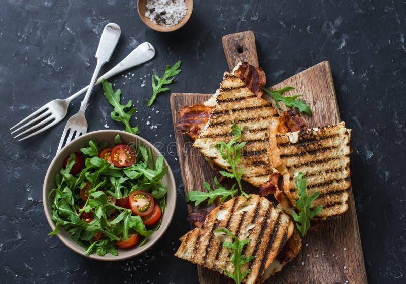 Bacon arrostito, panini della mozzarella sui taglieri di legno e rucola, insalata del pomodoro ciliegia su fondo scuro, vista sup immagini stock libere da diritti