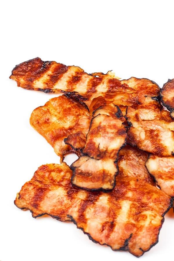 bacon arrostito su bianco Bacon cucinato croccante sulla Tabella Alimento non sano Rischio di obesità Barbecue casalingo fotografie stock