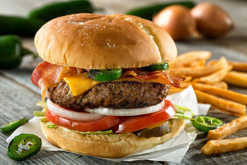 Bacon Cheddar Jalapeno Burger. A delicious burger with bacon, cheddar, jalapeno pepper, tomato, onion, pickle and lettuce with french fries royalty free stock photos
