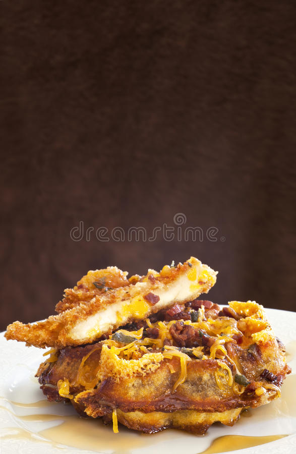 Bacon-Cheddar Waffles with Fried Chicken. A breakfast of bacon-cheddar waffles with fried chicken and golden syrup, on a white plate, with a mottled brown stock photography