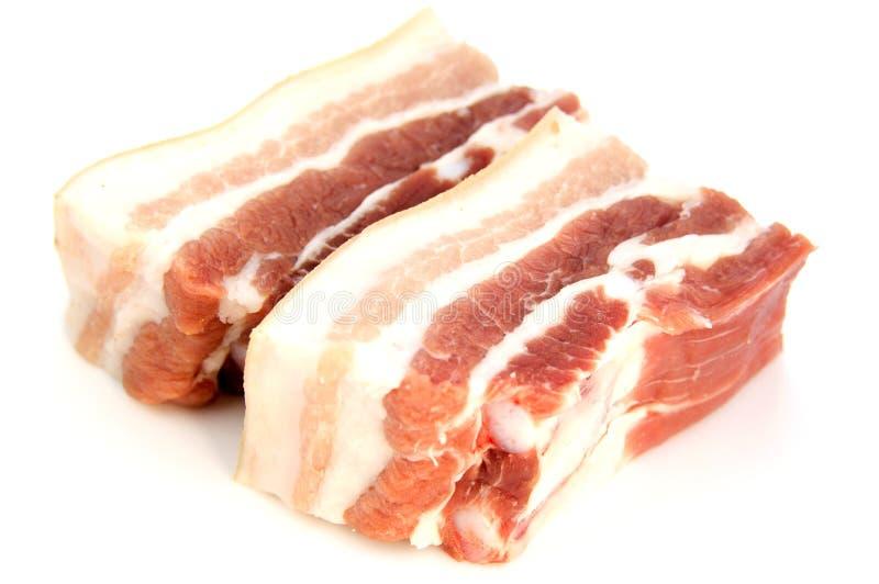 Bacon della carne di maiale su un fondo bianco fotografie stock