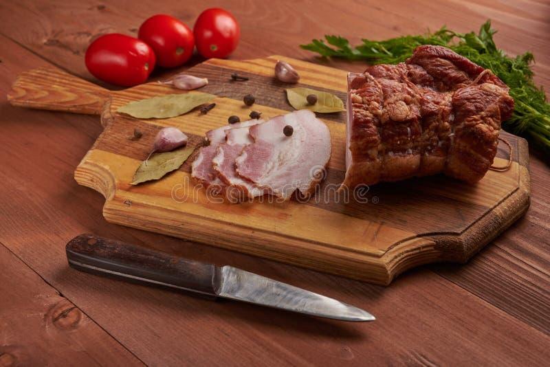Bacon e temperos em uma tabela de madeira imagem de stock