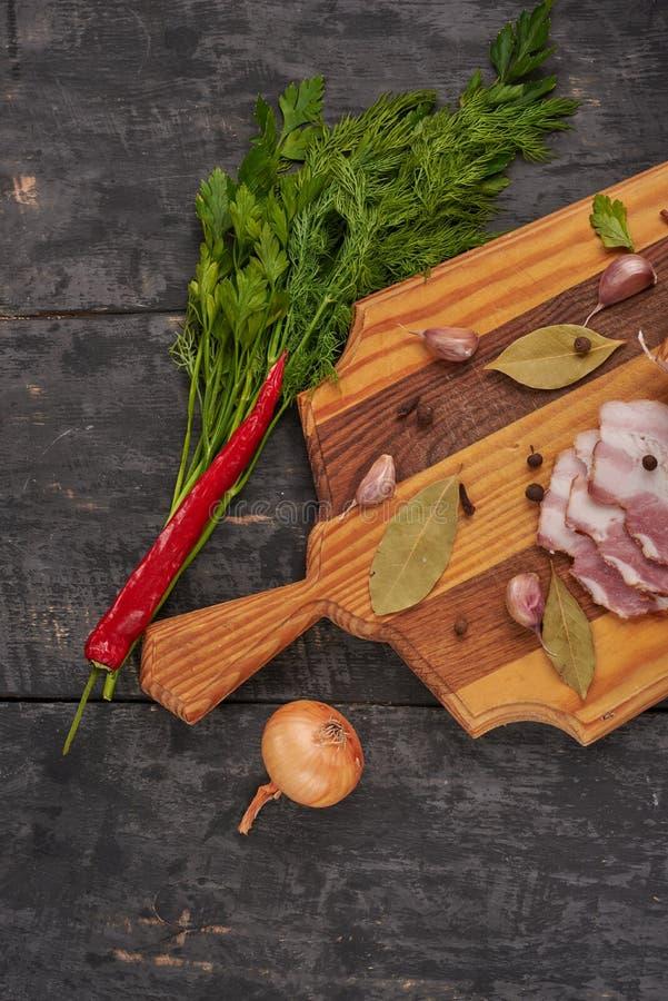 Bacon e temperos em uma tabela de madeira imagens de stock