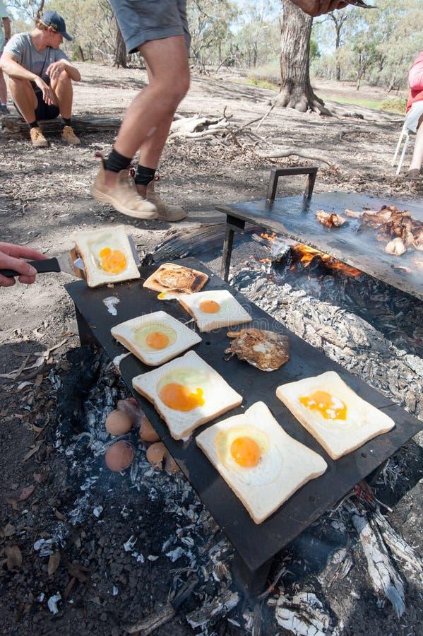 Bacon ed uova o rospo in un foro che è cucinato sul fuoco aperto del campo fotografia stock libera da diritti