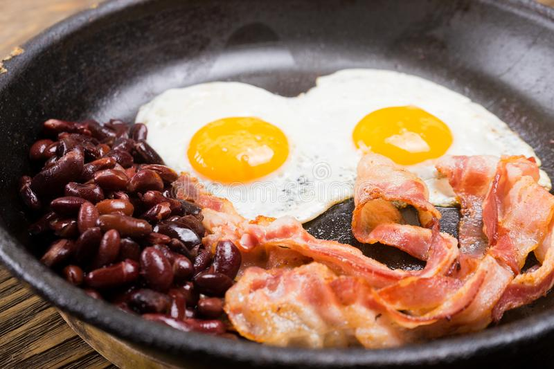 Bacon,Egg and bean. Salted egg and sprinkled with black pepper. English breakfast. Grilled bacon, two eggs and beans in pan on woo royalty free stock images