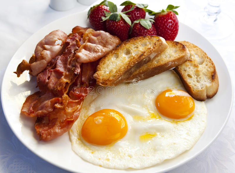 Bacon and Eggs. With toasted croutons and strawberries. A delicious breakfast stock photography