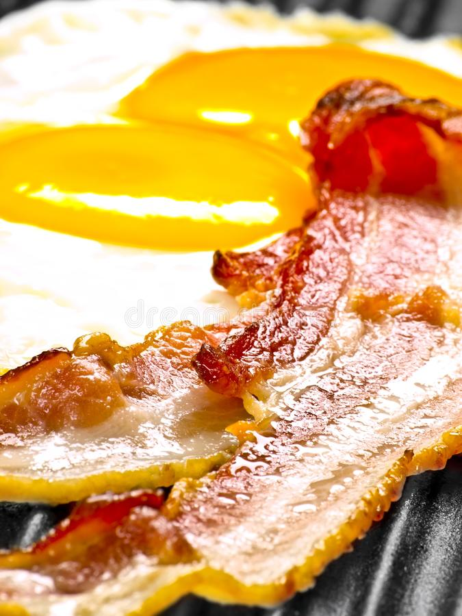 Bacon and eggs. Close up of bacon and eggs in a pan royalty free stock images