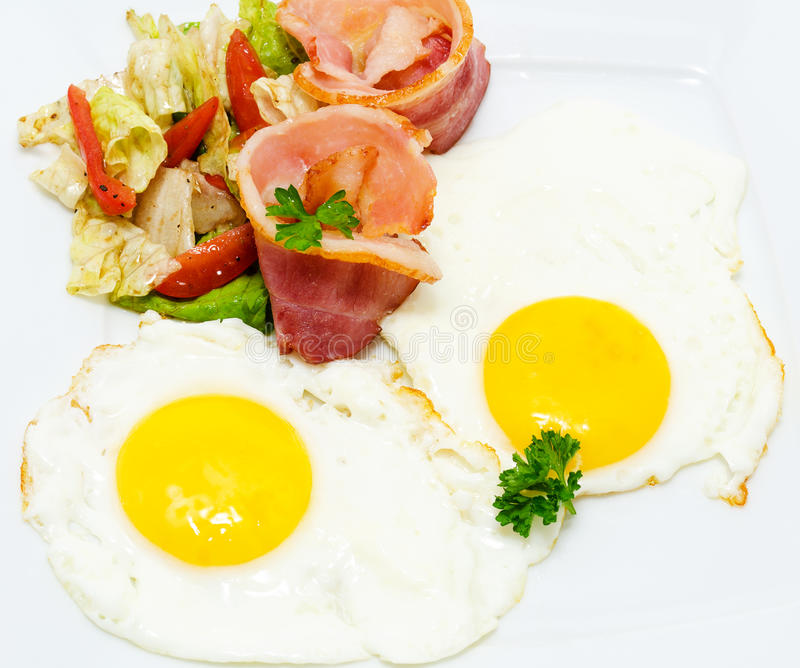 Bacon with eggs. Fried bacon and eggs with vegetable salad stock photography