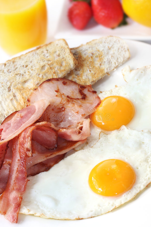Bacon and Eggs. For breakfast, with toast, orange juice and fresh fruit stock image