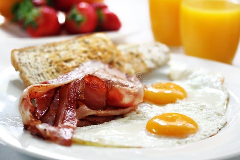 Bacon and Eggs. With toast, orange juice and fresh fruit. Shallow DOF stock photo