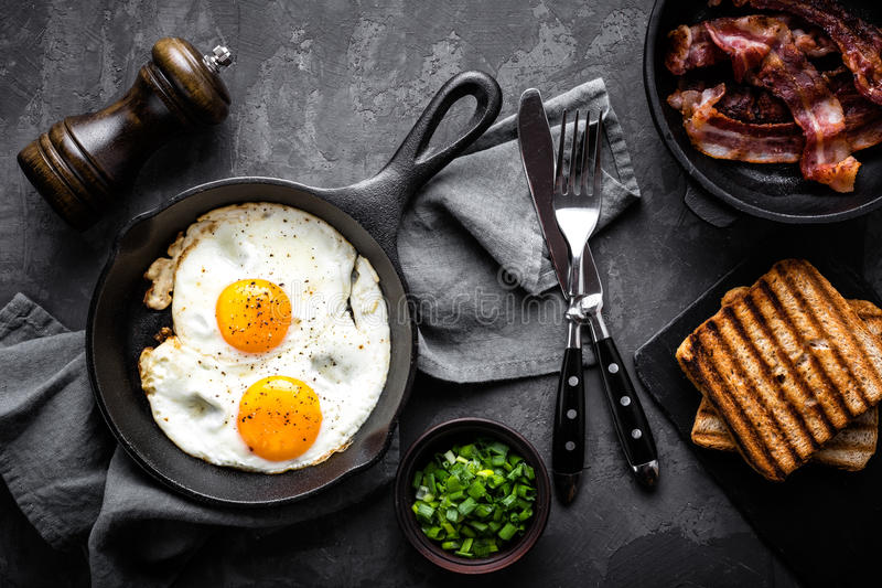 Bacon and eggs. On dark stone background royalty free stock photos
