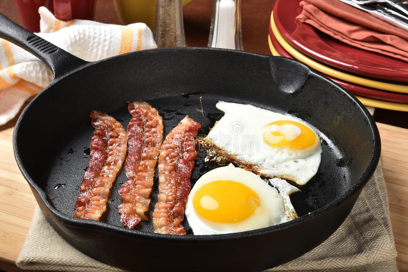 Bacon and eggs. Bacon and fried eggs in a cast iron skillet royalty free stock photo
