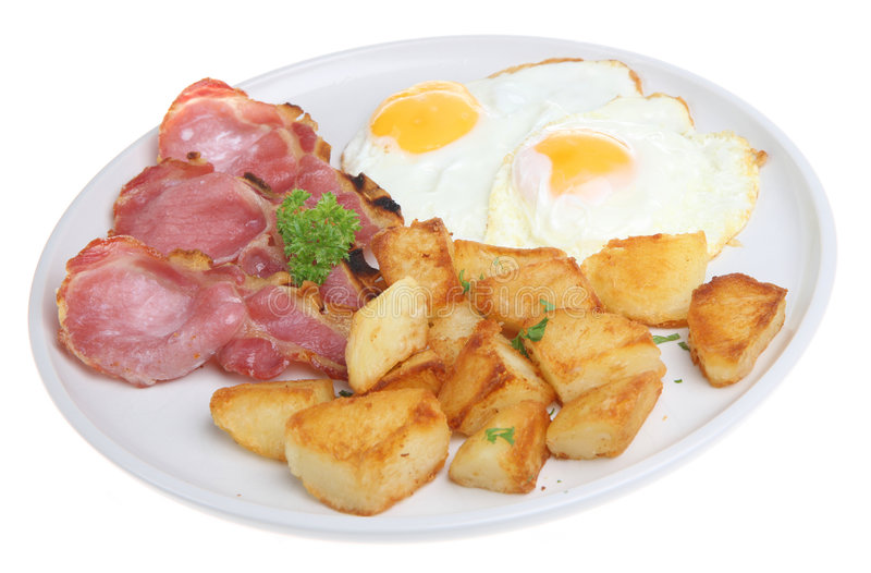 Bacon, Eggs & Fried Potatoes. Grilled back bacon with fried eggs and sauteed potatoes royalty free stock photos