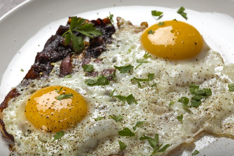 Bacon and eggs with ground pepper and parsley leaves. Close up view stock photos
